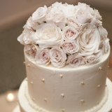 The wedding cake is topped with blush-colored roses.