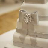 A silver bow with pearl details adorns the white wedding cake.