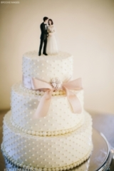 White Wedding Cake with Pearl Detailing and a Pink Bow / Brooke Images / Epping Forest Yacht Club /