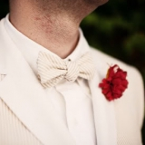 tan seersucker suit and red pom pom boutonniere