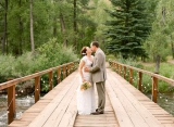 bride groom kissing on bridge