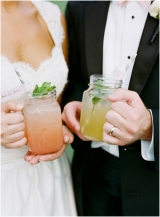 signature cocktails in mason jars bride and groom toast
