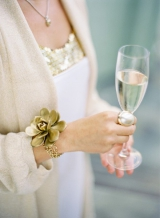 woman bride holding champagne glass gold flower chain bracelet