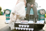Bride and groom pose on turquise classic car