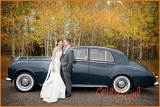 Bride and groom pose with classic car and fall leaves
